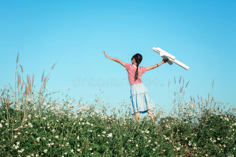 Pilot girl child imagine to future playing toy air plane at outdoor nature paddy filed with mountain vintage sky background. stock photo