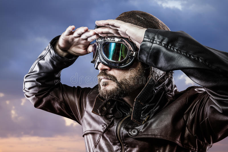 Pilot with glasses and vintage hat with proud expression looking. At the horizon, war stock photography