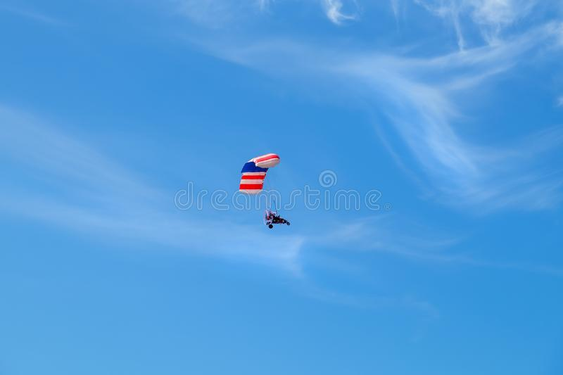 Pilot hang gliding on a blue sky. royalty free stock images