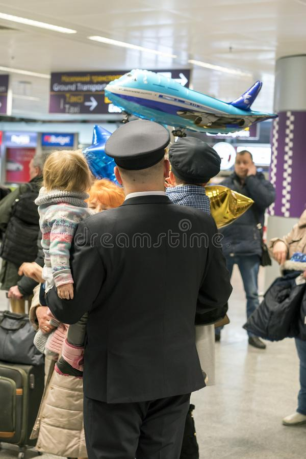 Pilot with his family at the airport. The child is in the hands of the pope. royalty free stock image