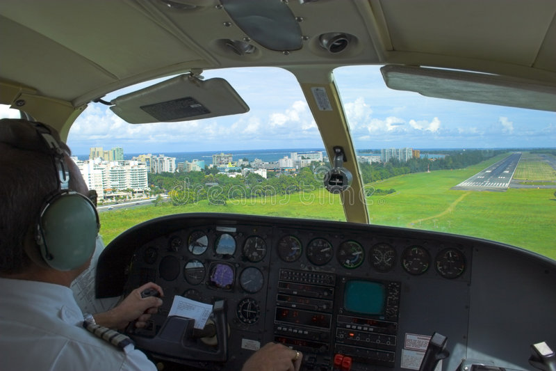 Pilot landing. Pilot is getting ready for landing overlooking the city, ocean, beach and landing strip on the background royalty free stock image