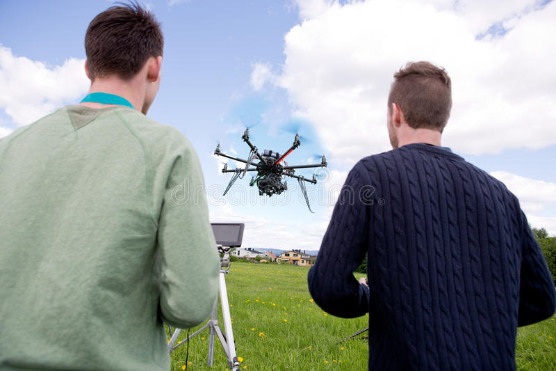 Pilot and Photographer Operating Photography Drone. A pilot and photographer operating a UAV photography drone in an open field royalty free stock image
