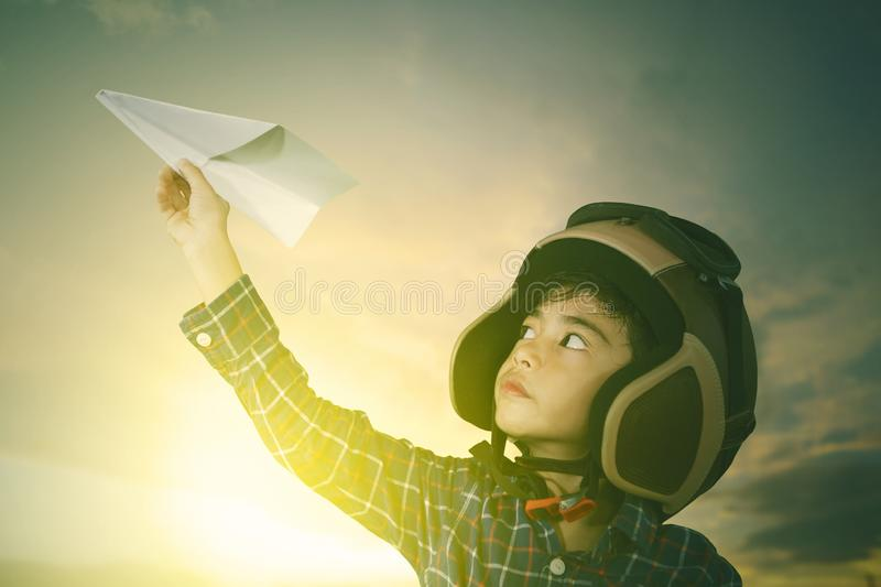 Pilot playing a paper plane in sunrise background stock photo