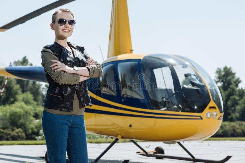 Pilot- posera för nätt kvinnlig nära helikoptern arkivfoto