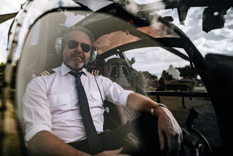 Pilot- sammanträde i cockpiten av en privat helikopter fotografering för bildbyråer