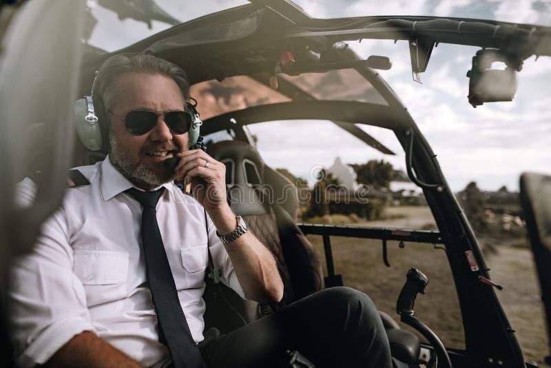 Pilot- samtal för lycklig helikopter på hörlurar med mikrofon royaltyfri fotografi
