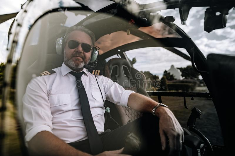 Pilot sitting in the cockpit of a private helicopter stock image