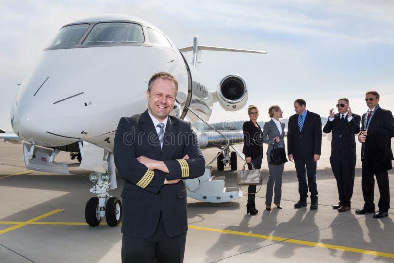 Pilot- stående framme av den företags privata strålen arkivbilder