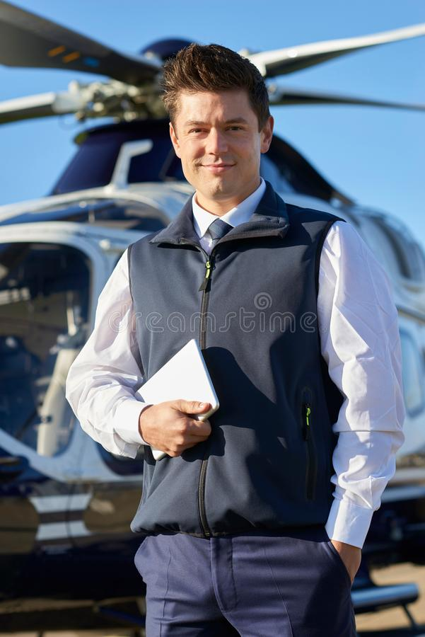 Portrait Of Pilot Standing In Front Of Helicopter With Digital T stock photos