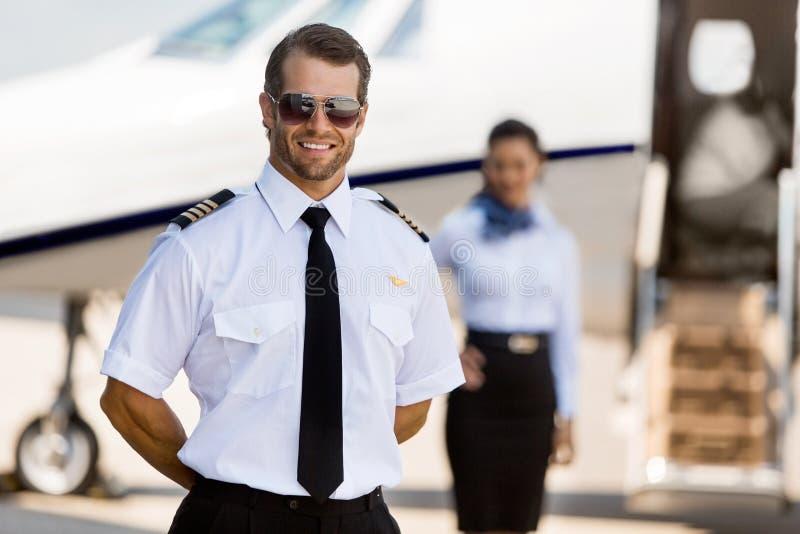 Pilot Standing With Stewardess och privata Jet At royaltyfri foto