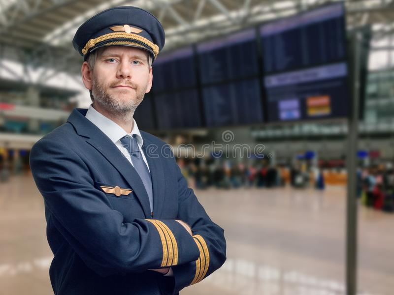 Pilot in uniform with golden stripes and cap crossed his arms while standing in the airport royalty free stock photo