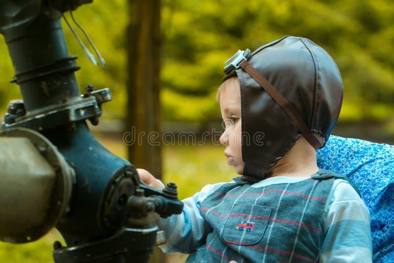 Pilota del bambino nel casco dell'aviatore che si siede all'ingranaggio del metallo fotografia stock