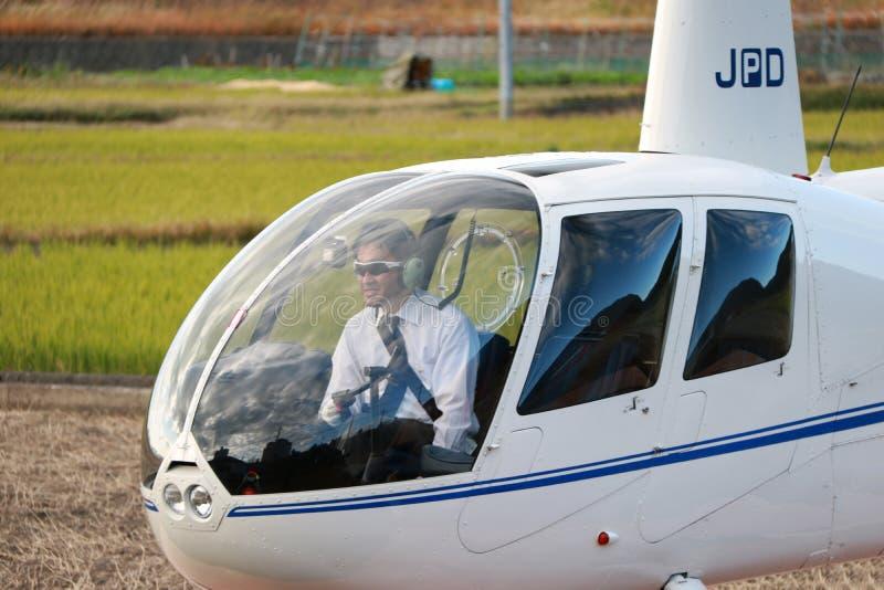 Pilota dell'elicottero nell'elicottero JA002R - ROBINSON R44 RAVEN di viaggio da Robinson Helicopter Company fotografia stock