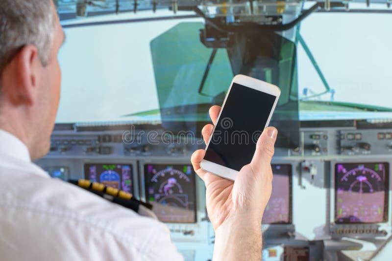 Pilota di linea aerea che per mezzo dello Smart Phone immagine stock