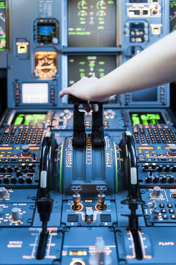 Pilotagem em uma cabina do piloto do avião com as alavancas empurradas com mão na parte superior para a decolagem fotografia de stock
