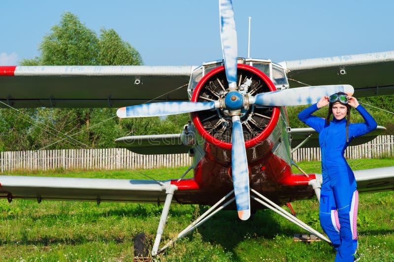 Pilote de femme dans le casque se tenant avec l'avion images libres de droits