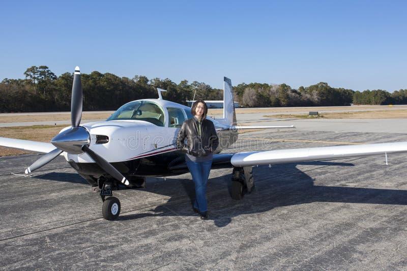 Pilote féminin avec l'avion privé image stock