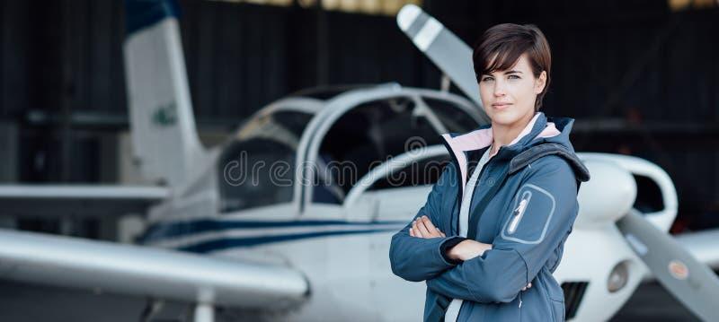 Pilote féminin de sourire posant avec son avion photo stock
