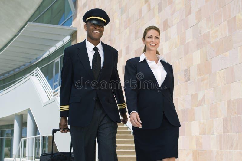Pilote And Flight Attendant marchant à l'extérieur du bâtiment image stock