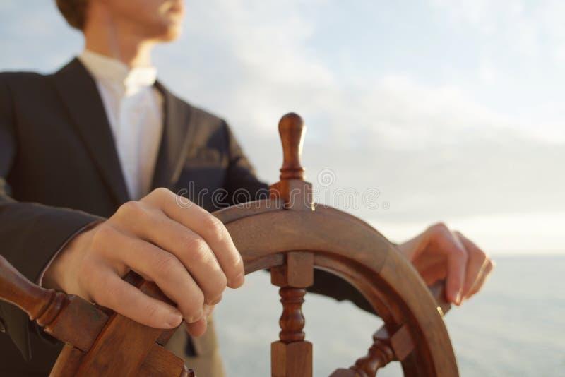 pilote Mains sur le gouvernail de direction de bateau image stock