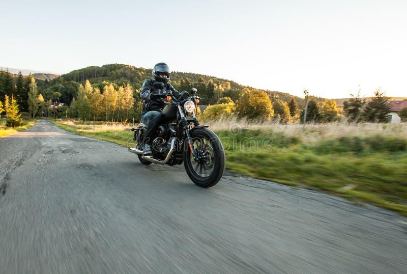 Pilote-siège sur la moto sur le chemin forestier photographie stock libre de droits