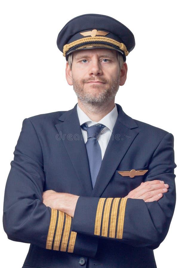 Piloten i kaptenlikformig med 4 guld- band och lock korsade hans armar arkivfoto