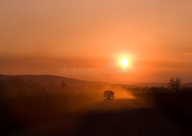 Piloter de véhicule au coucher du soleil image libre de droits