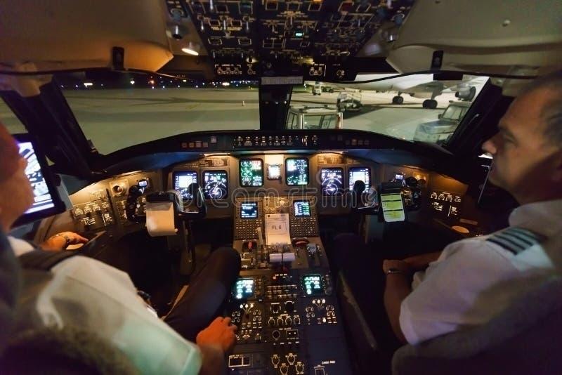 Piloter i flygplancockpit arkivbild