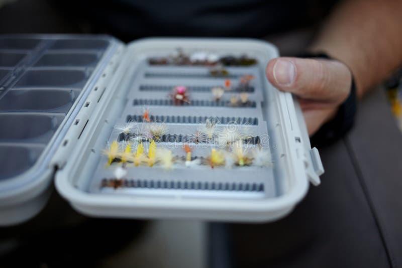 Piloti il pescatore che controlla la sua scatola di attrezzatura per vedere se ci sono mosche fotografia stock