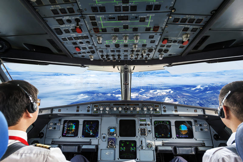 Piloti nella cabina di guida piana immagine stock