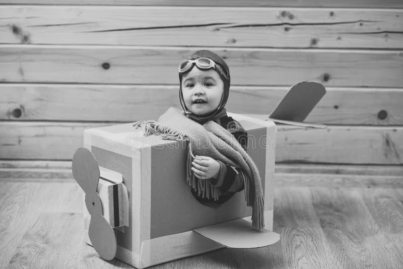 Piloto da criança Menino pequeno do sonhador que joga com um avião do cartão foto de stock