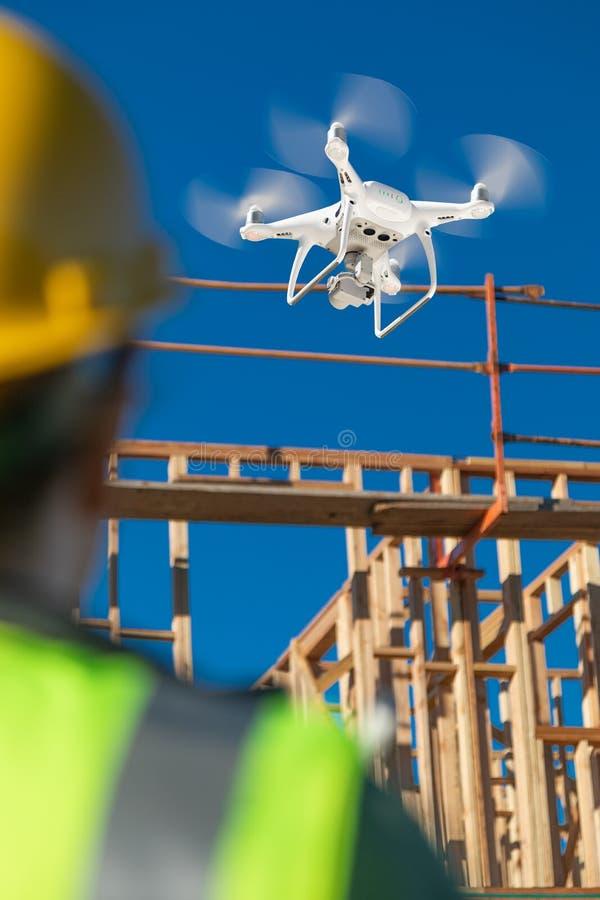 Piloto de sexo femenino Flies Drone Quadcopter que examina el emplazamiento de la obra foto de archivo
