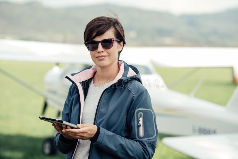 Piloto de sexo femenino que usa una tableta imagen de archivo