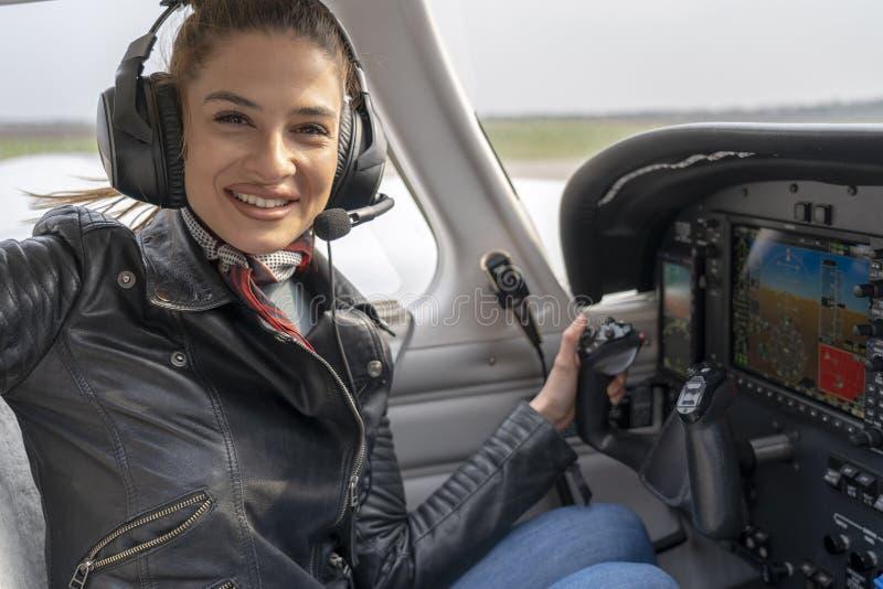 Piloto de sorriso With Headset Sitting da jovem mulher na cabina do piloto do avião fotos de stock