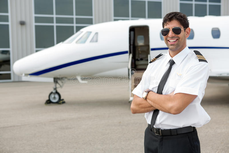Piloto de sorriso Standing In Front Of Private Jet imagem de stock royalty free