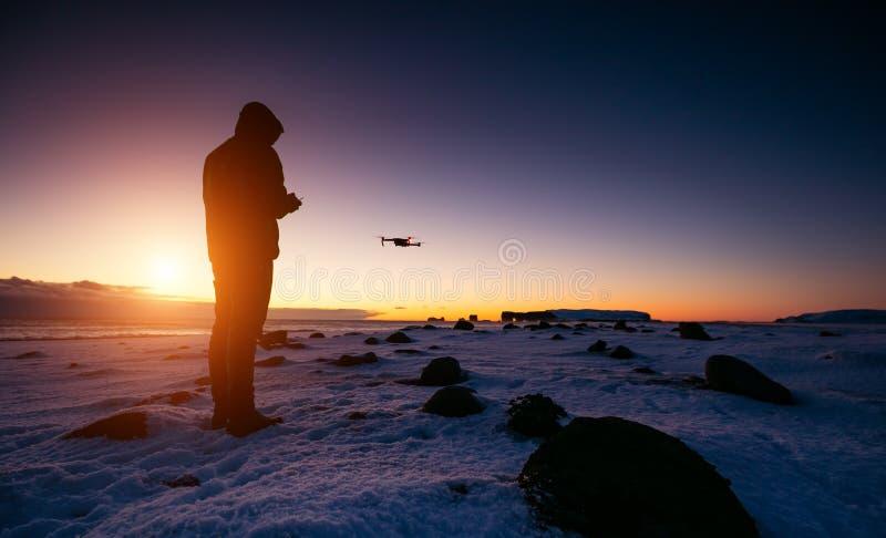 Piloto del abejón con los aviones sin tripulación en ligt hermoso de la puesta del sol imagenes de archivo