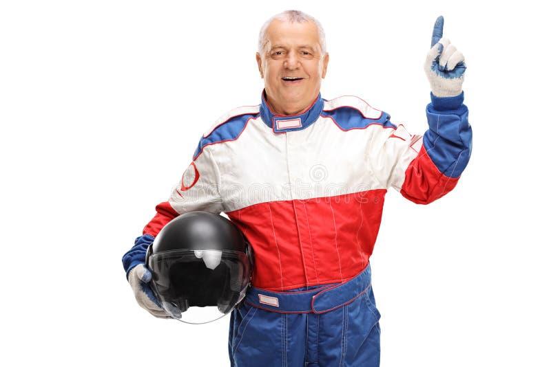 Piloto do carro que guarda um capacete e que aponta acima imagens de stock royalty free