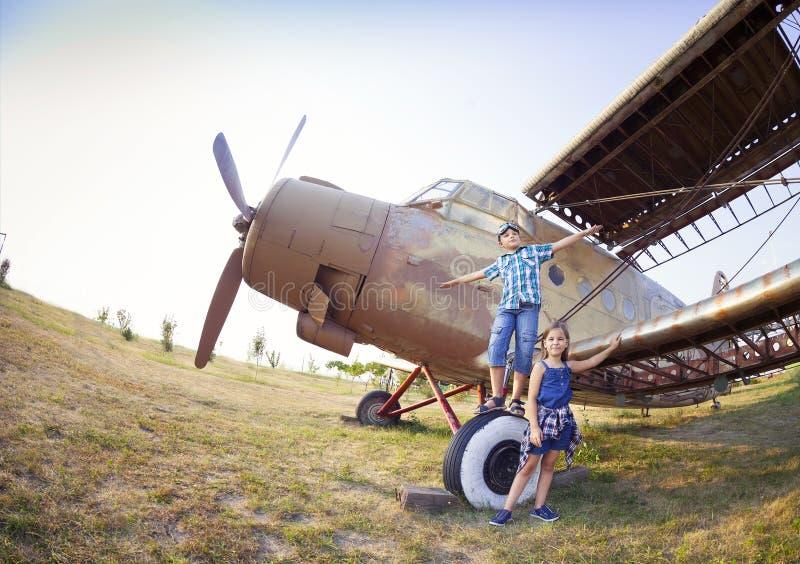Piloto do rapaz pequeno e da menina perto do avião retro imagens de stock royalty free