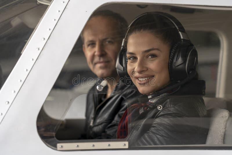 Piloto e instrutor fêmeas de sorriso do voo em uma cabina do piloto de aviões fotos de stock