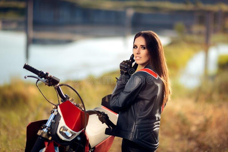 Piloto fêmea do motocross ao lado de sua motocicleta imagem de stock