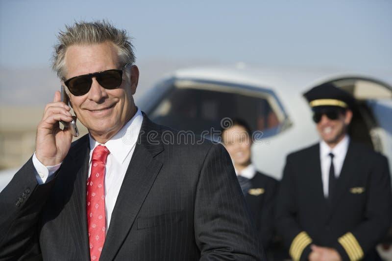 Piloto And Flight Attendant de On Call With do homem de negócios no fundo fotografia de stock