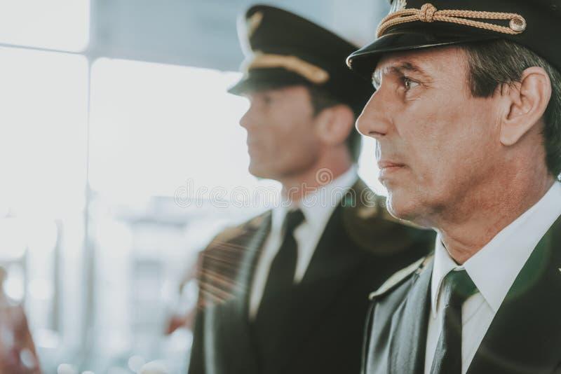 Piloto hermoso y situación joven del copiloto en el aeropuerto imágenes de archivo libres de regalías