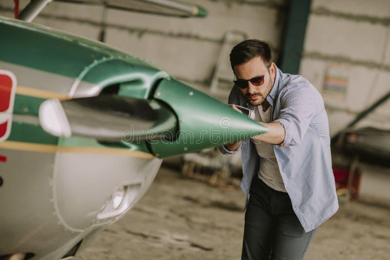 Piloto joven que comprueba el aeroplano ultraligero antes de vuelo imagen de archivo libre de regalías