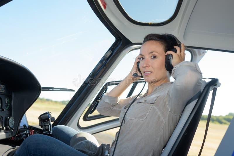 Piloto serio de la mujer joven en las auriculares que se sientan en el avión fotografía de archivo libre de regalías