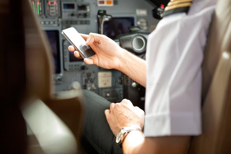 Piloto Using Cell Phone na cabina do piloto fotografia de stock royalty free