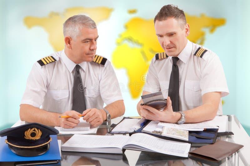 Pilotos da linha aérea que enchem-se nos papéis em ARO foto de stock