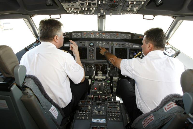 Pilotos do avião na cabina do piloto que prepara-se à decolagem