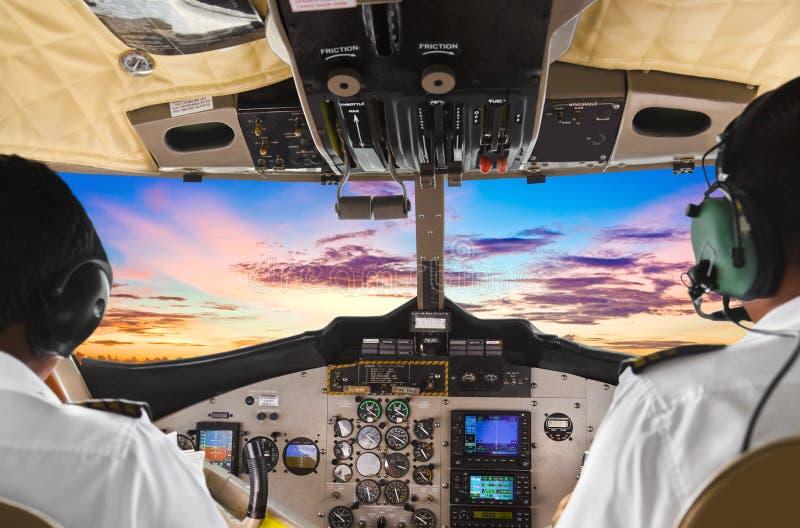 Pilotos na cabina do piloto e no por do sol planos foto de stock royalty free