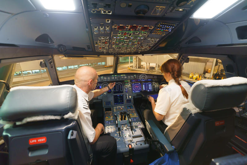 Pilots in aircraft cockpit. HELSINKI - SEPTEMBER 20: Finnair pilots preparing aircraft for take-off from the airport on September 20, 2014 in Helsinki, Finland stock photo