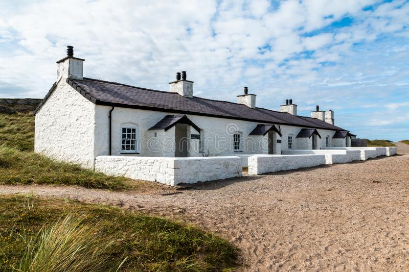 Pilots Cottages Llanddwyn Island. The row of four small cottages on Llanddwyn Island was built for the pilots who helped boats navigate into the ports along the royalty free stock image